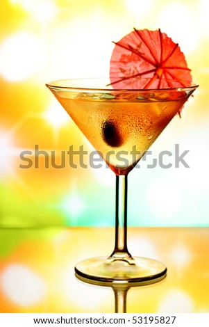 Cocktail glass with umbrella and holiday lights in the background