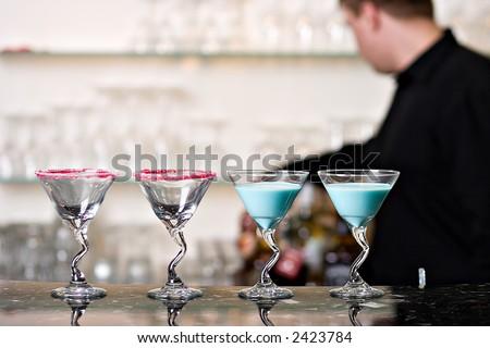 Cocktail glasses on bar, with bartender
