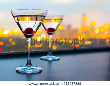 Cocktail glasses with city view.
