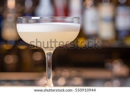 Cocktail in Margarita glass, pale dogwood pink color, with foam on top, selective focus