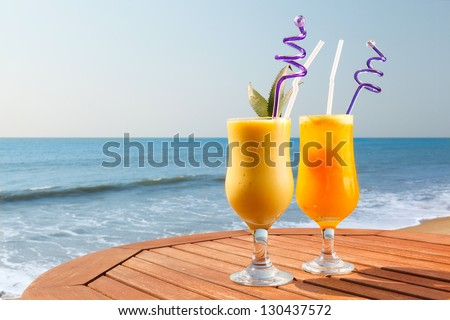 cocktail of pineapple, mango and passion fruit juice with ice on the table