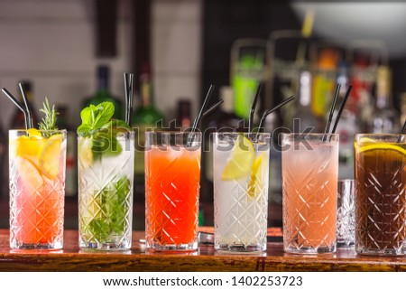 Cocktail on the bar. Whiskey-cola cocktail, pina colada, mojito-cocktail, orange cocktail, strawberry cocktail in glass glasses with straws. Bar accessories: shaker, spoon, spices on a wooden stand