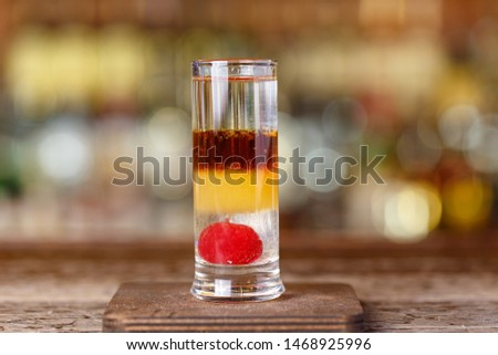 Cocktail on the basis of gin with apple liqueur, multi-layered multi-colored drinks on the blurred background of the bar