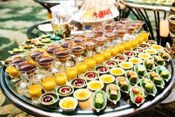 Cocktail party with variety of desserts and food decorated in spoons arranged in orderly fashion