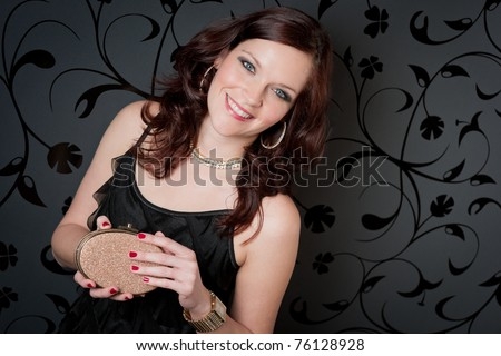 Cocktail party woman wear evening dress hold handbag on black background - stock photo