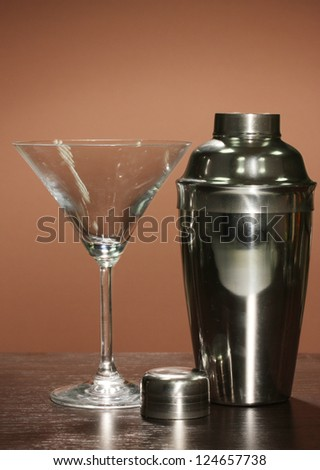 Cocktail shaker and cocktail glass on color background
