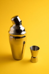 Cocktail shaker kit on yellow background. Cobbler cocktail shaker. Vertical image. Metal cocktail shaker isolated