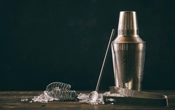 Cocktail shaker, swizzle, tongs and spoon with crushed ice for preparing a summer cocktail beverage on an old vintage wooden table with copy space