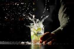 Cocktail splash with ice cubes and lime. Preparing of the delicious fresh cocktail on the bar stand