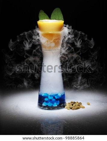 cocktail very impressive with dry ice and smoke in a black background with gradient around