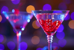 Cocktail with casino dice in glass against blurred lights, closeup. Space for text