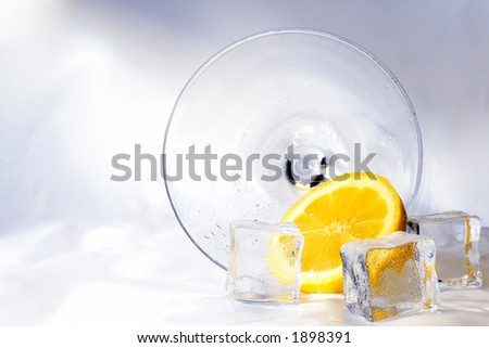 Cocktail with ice and lemon on its side - stock photo