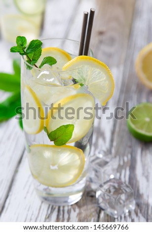 Cocktail with ice and lemon slices isolated on white background