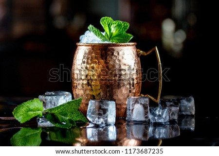 Cocktail with ice, in a copper mug on a black background. #1173687235