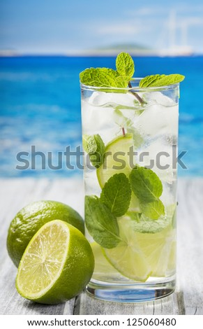 cocktail with lime and mint on a beach
