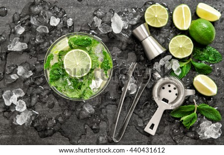 Cocktail with lime, mint and ice. Bar drink accessories on black table background. Alcoholic and nonalcoholic cold drinks. Selective focus