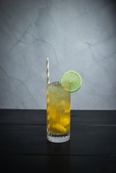 Cocktail with muddled lemon in a highball
