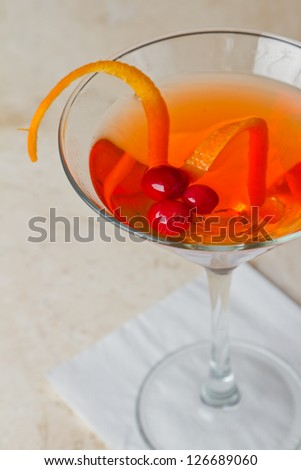 cocktail with orange and cranberries served on a bright bar