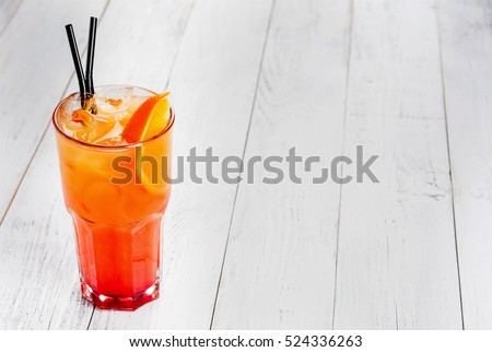 Cocktail with orange juice and ice cubes on white background. #524336263