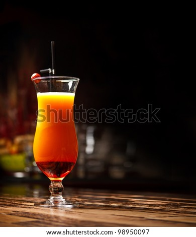 Cocktail with orange Juice on bar table, cherry decoration