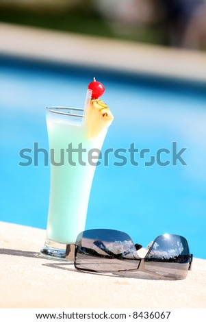 cocktail with sunglasses on the edge of the swimming pool