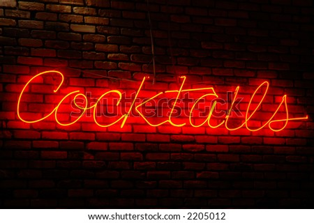 Cocktails neon sign illuminated against a brick wall at night