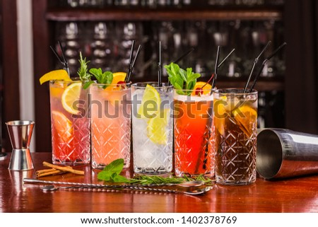Cocktails on the bar. Whiskey-cola cocktail, pina colada, mojito-cocktail, orange cocktail, strawberry cocktail in glass glasses with straws. Bar accessories: shaker, spoon, spices on a wooden stand