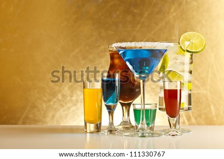 Cocktails with alcohol on grungy gold background