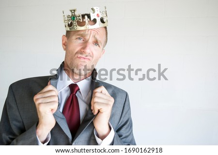 Cocky businessman wearing golden jeweled crown popping his collar with an arrogant expression Stock fotó ©