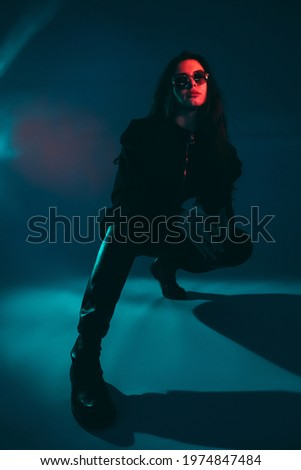 Cocky girl. Underground fashion. Cyberpunk streetstyle. Tough swag red neon light woman in black leather boots sunglasses sitting on hunkers on dark night blue background. Stockfoto ©