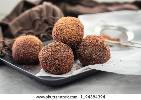 Cocoa balls, chocolate balls cakes in a black tray, sprinkled with cocoa powder.
