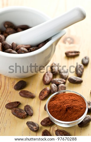 cocoa beans and cocoa powder on wooden table