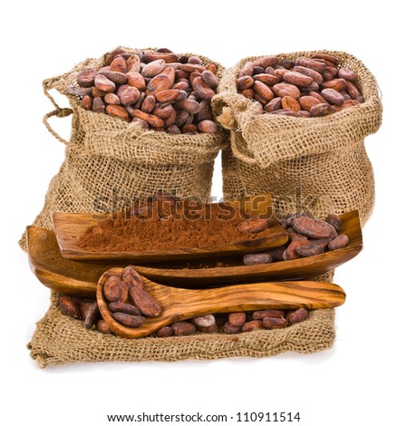 cocoa beans in bags of linen, cocoa powder on wooden stand with wooden spoon isolated on white background