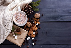Cocoa, coffee, gift, fir branch, nuts, cones, cozy knitted blanket. Winter, New Year, Christmas still life.