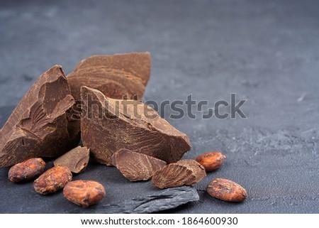 Cocoa liquor mass, beans on slate stand, gray concrete background. Confectionery, menu, recipe concept. Close-up, copy space