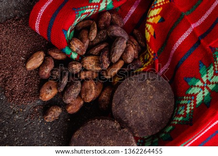 Cocoa, mexican chocolate and cacao powder on a traditional metate, used to extract the powder from the cacao beans or cacao nibs