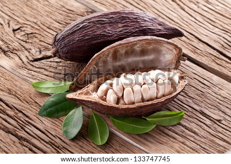Cocoa pod on a dark wooden table. - stock photo
