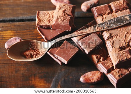 Cocoa powder and dark chocolate on color wooden background