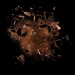 Cocoa powder with chocolate pieces and curls explosion on black backgrounds