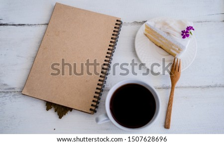 Coconut Cake and black coffee  with a brown book and pen set together on the desk. Concept copy space and working with break breaks