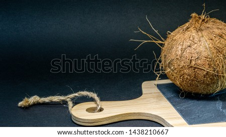 Coconut exotic fruit, fruits in the shell on a stone kitchen board with wooden handle blackboard, dark background, selective focus, selective light, closeup #1438210667