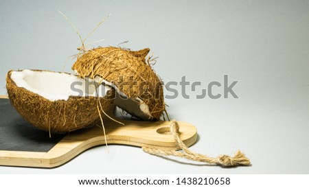 Coconut exotic fruit, two halves of fruit shell on a stone kitchen board with wooden handle blackboard, with a bright background, selective focus, selective light, close-up #1438210658
