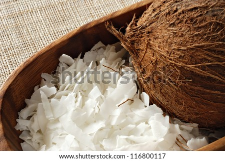 Coconut flakes with whole coconut in wooden bowl.  Macro with shallow dof.