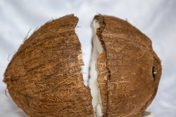 Coconut half on a white background. Top view of a healthy, tropical, delicious fruit. Fresh traditional exotic food full of micronutrients. Cracked coconut half.