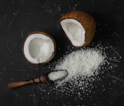 Coconut halves with shell with pulp. Coconut shavings on dark black background. Wooden spoon for Coconut shavings. Top view.
