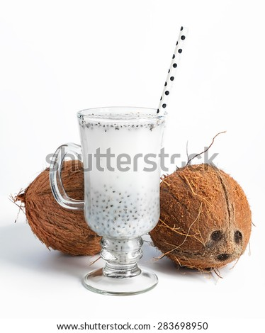 Coconut milk with chia seeds served in glass with white paper polka dot straw. Cold and refreshing drink. On white background. Selective focus.