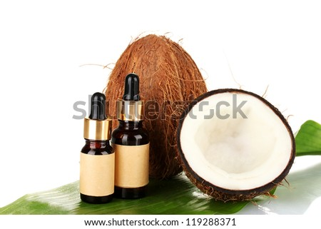 coconut oil in bottles with coconuts on white background