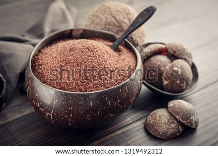 Coconut palm granulated sugar in a bowl with jaggery coconut on wooden background closeup