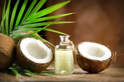 Coconut palm oil in a bottle with coconuts and green palm tree leaf on brown background. Coco nut close-up. Healthy Food, skin care concept. Skincare treatments. Vegan food