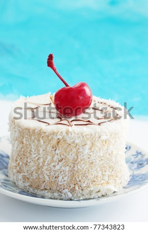Coconut  pastry with the cream and the cherries